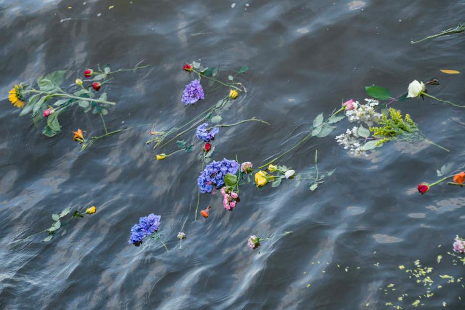 Bei einer Demonstration für Seenotrettung warfen Menschen Blumen ins Wasser.