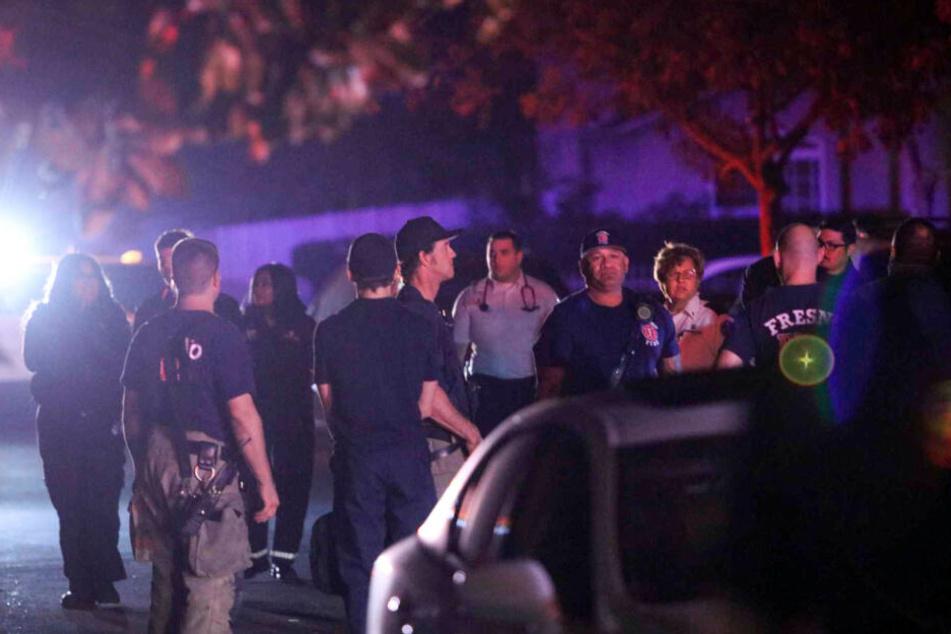 Einsatzkräfte von Polizei und Feuerwehr stehen auf einer Straße. Vier Menschen sind im US-Staat Kalifornien in einem Garten von einem Unbekannten erschossen worden.