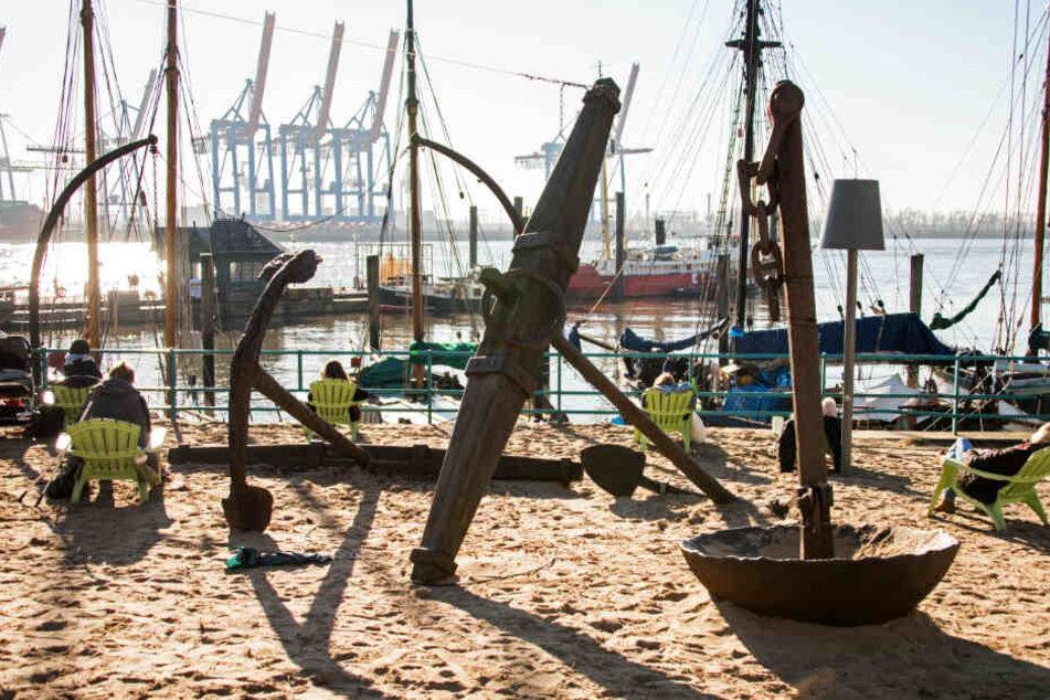Auf Stühlen im Sand genießen Menschen die Sonne am Museumshafen Övelgönne.