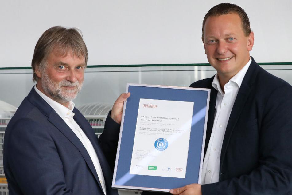 """Ralf-Rainer Braun (links), Vorsitzender der Jury Umweltzeichen """"Blauer Engel"""", überreicht Felix Eichhorn von Aida Cruises die Urkunde """"Blauer Engel""""."""