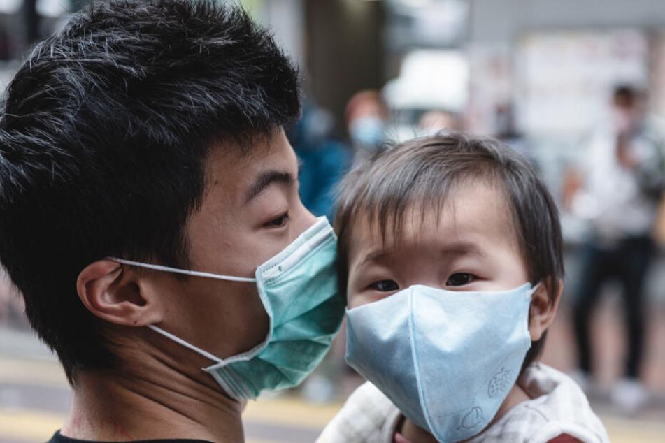 Ein Vater hält sein Kind auf dem Arm. Beide Personen tragen Atemschutzmasken.