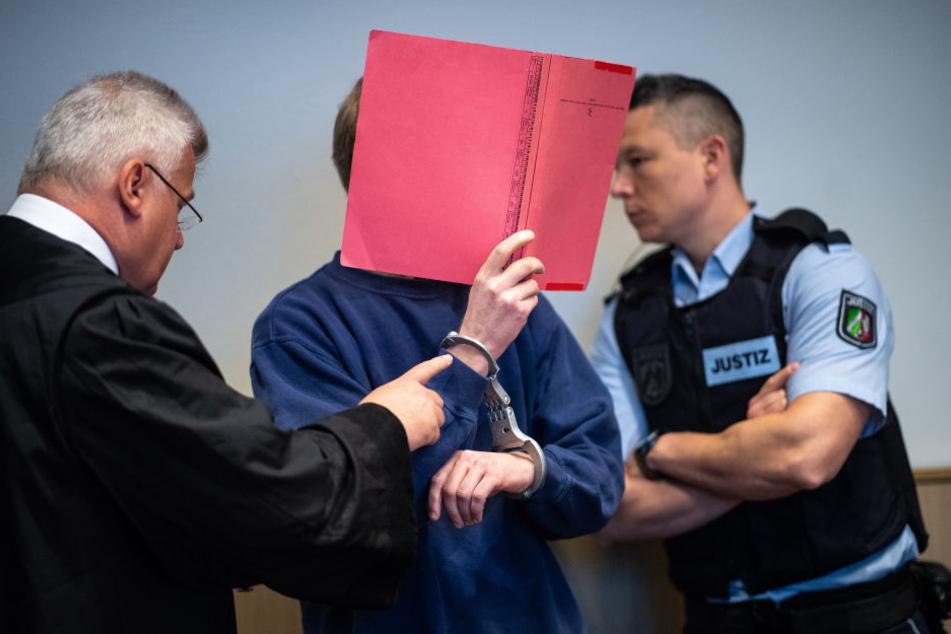 Der Angeklagte beim Prozessauftakt hinter einer roten Mappe.