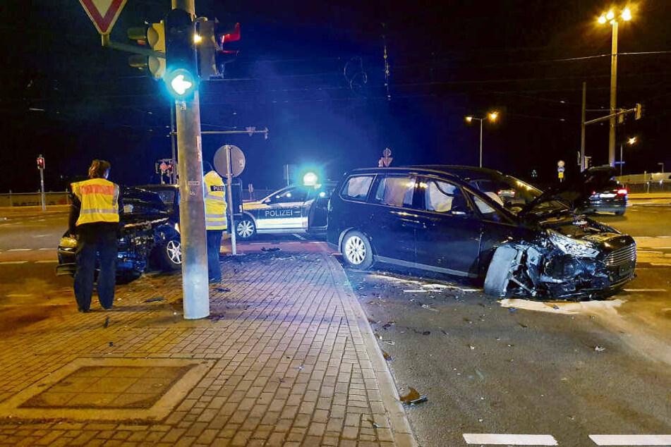 Polizisten stehen vor dem demolierten blauen Fiat (l.) des Unfallfahrers. In dem Wagen ließ er seine verletzte Familie zurück.