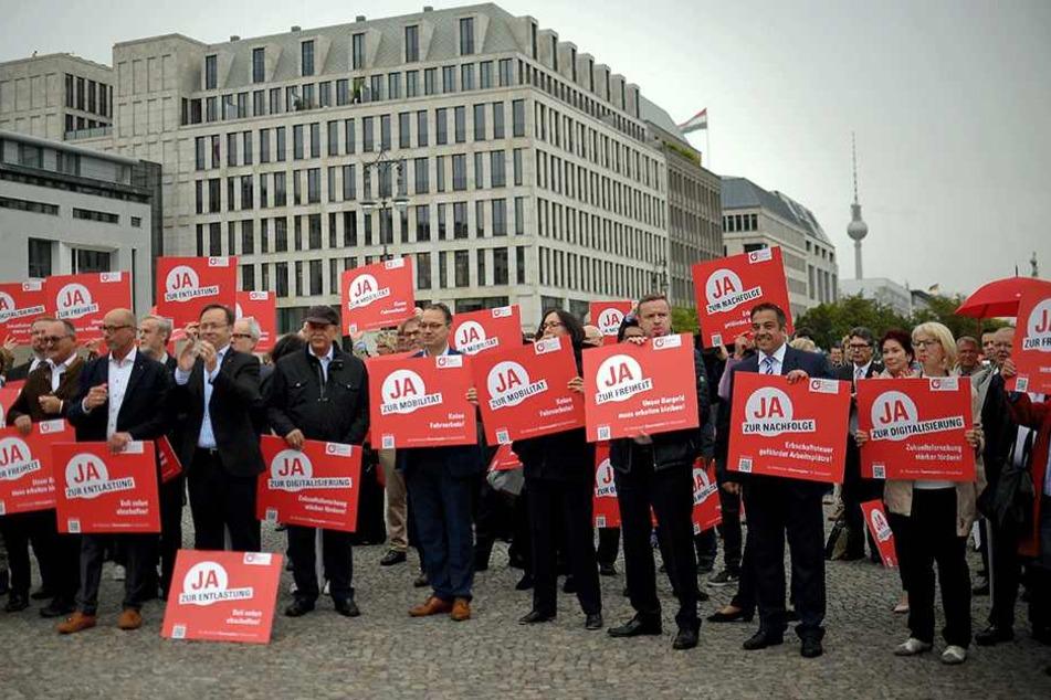 "Demonstranten stehen am 08. September vor dem Brandenburger Tor in Berlin bei der Aktion ""Mittelstand - Melkkuh der Politik""."