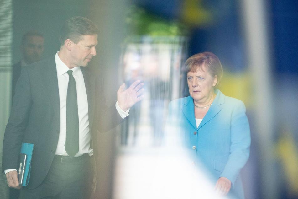 Bundeskanzlerin Angela Merkel (CDU) geht vor dem Empfang des irischen Präsidenten neben dem Regierungssprecher Steffen Seibert durch das Bundeskanzleramt.