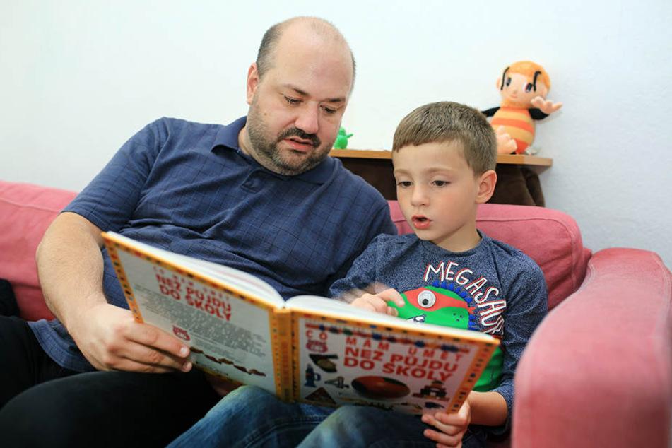 Petr Cizmar schaut mit seinem Sohn ein Kinderbuch an. David kann heute schon ein bisschen lesen - im August wurde er in Dresden eingeschult.
