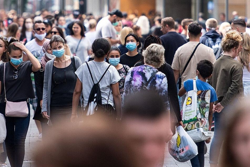 Zahlreiche Menschen mit Masken sind auf der Schildergasse, einer der Haupteinkaufsstraßen Kölns, unterwegs.