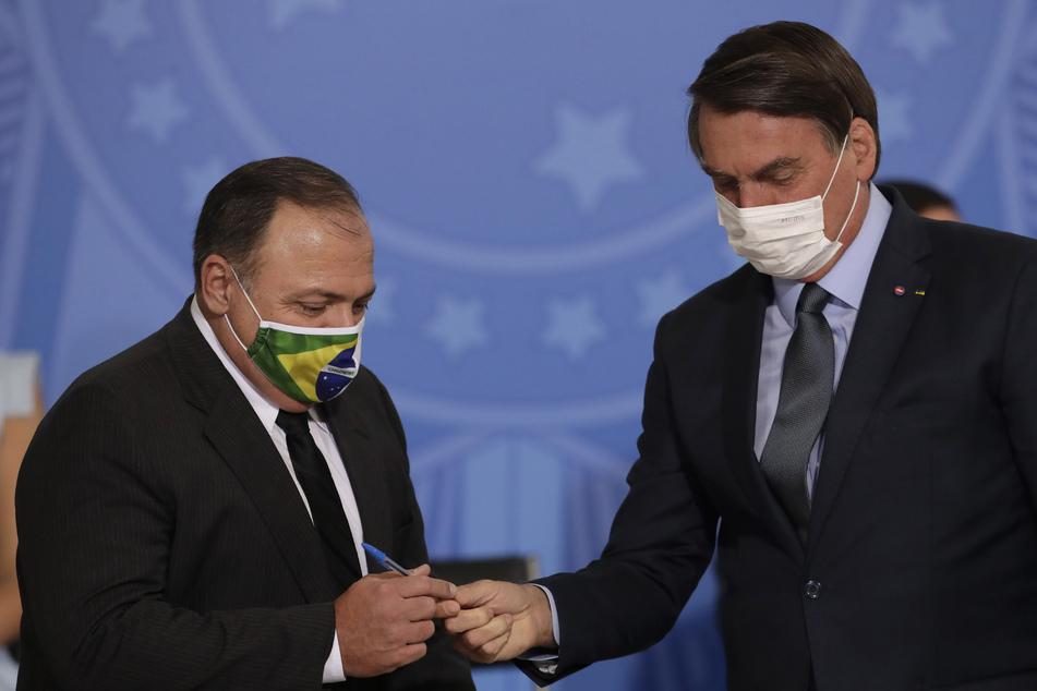 Brasiliens Präsident Jair Bolsonaro (r.) überreicht seinem neuen Gesundheitsminister Eduardo Pazuelo einen Stift.