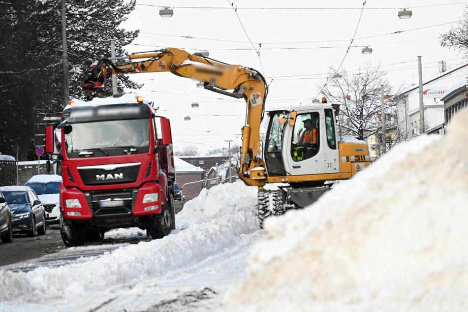Mit einem Bagger werden in Kassel die Schneemengen von den Straßenbahngleisen entfernt.