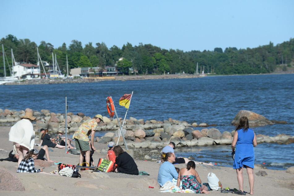 Menschen sonnen sich am Strand von Helsinki einen Tag nach der Sommersonnenwende.