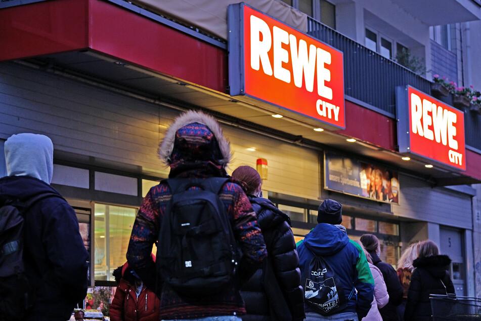 Menschen stehen vor einem Supermarkt an, da sich nur eine bestimmte Anzahl von Kunden gleichzeitig im Laden aufhalten darf. Sie müssen künftig Masken tragen.
