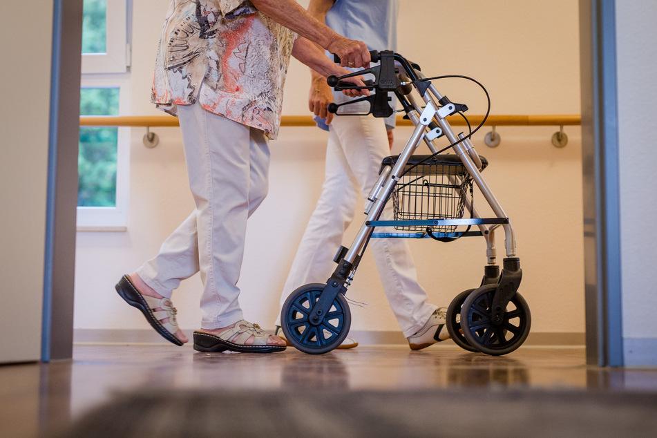 Eine Pflegekraft geht in einem Pflegeheim mit einer älteren Frau über einen Korridor.