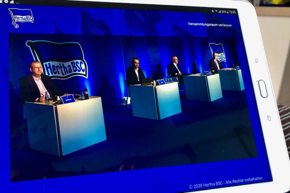 Das Podium mit Herthas Finanz-Geschäftsführer Ingo Schiller (l) und Hertha-Manager Michael Preetz (2.v.l.), ist bei der digitalen Mitgliederversammlung von Hertha BSC auf einem Tablet zu sehen.