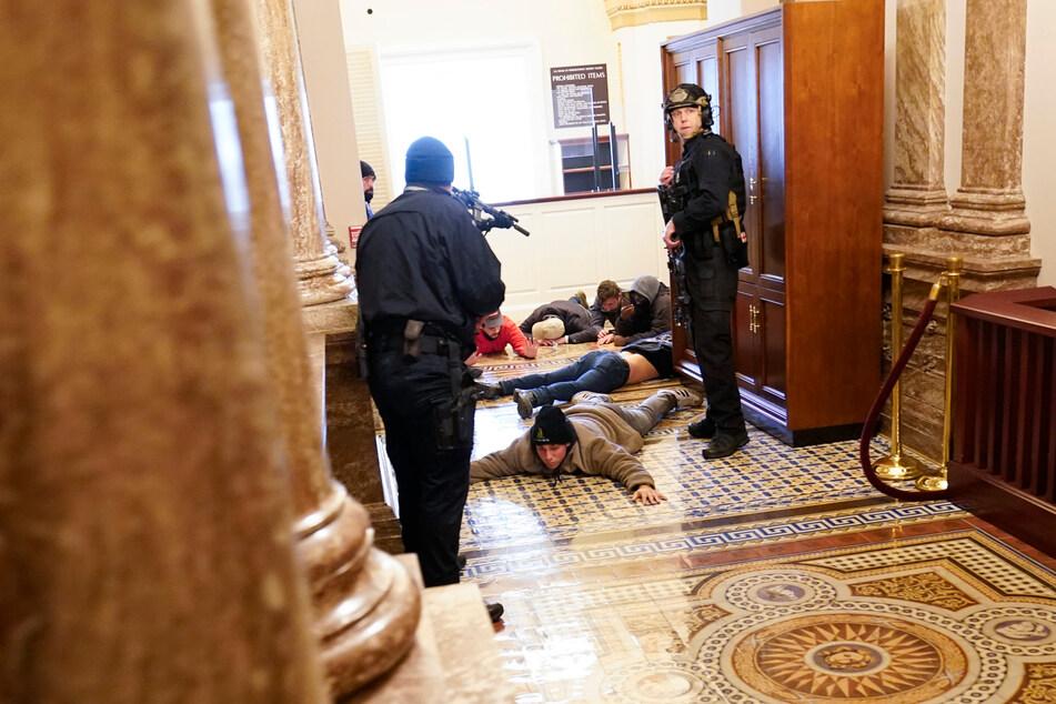 6. Januar 2021: Die US-Kapitol-Polizei hält Demonstranten mit vorgehaltener Waffe fest, nachdem das Gebäude gestürmt worden war.