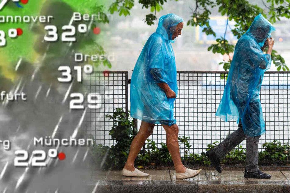 Passanten laufen in Regencapes durch Berlin.
