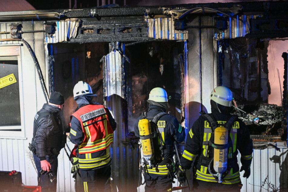 Polizei und Feuerwehr inspizieren die Schäden nach den Löscharbeiten.