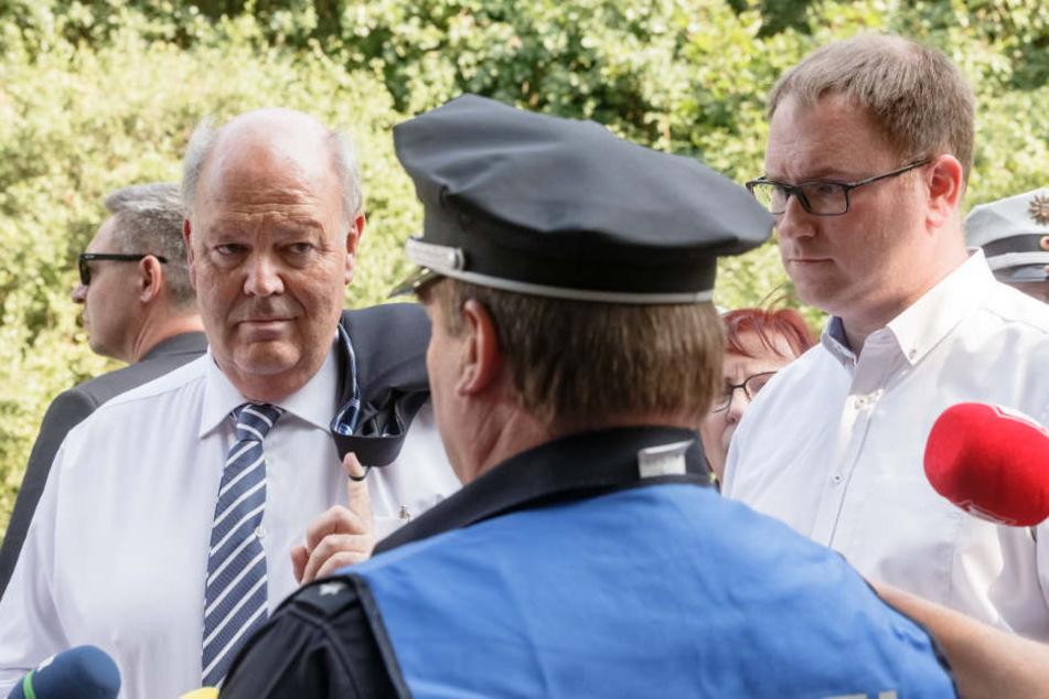 Hans-Joachim Grote (links), Innenminister Schleswig-Holsteins, und Jan Lindenau, Bürgermeister von Lübeck, lassen sich am Tatort von der Polizei informieren.