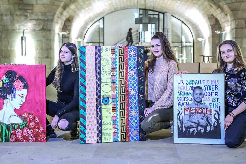 Die Gymnasiastinnen Larissa Witczak (17), Elisabeth Koch (17) und Anne Müller (18, v.l.) zeigen drei ihrer Bilder, die bis Montag in der Unterkirche der Frauenkirche zu sehen sind