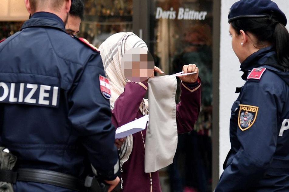 Polizisten kontrollieren eine verschleierte Frau in Österreich (Symbolbild).
