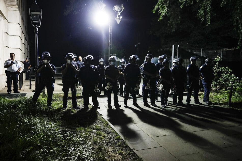 Polizisten in New York beobachten Demonstranten, die sich in einem Protestcamp vor dem Rathaus versammeln. Die Proteste gegen Polizeigewalt in den USA ebben kaum ab.