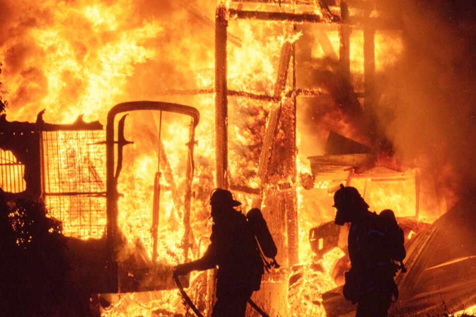 Zwei Feuerwehrleute stehen vor einem Flammenmeer in Tostedt.