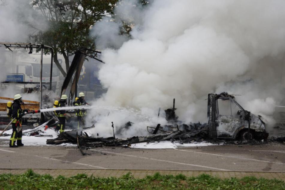 Feuerwehrleute löschen das Wohnmobil mit einem Schlauch.