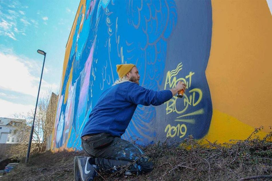 """Fertig! Zum Abschluss seiner Arbeit sprüht Simon Rosenow seinen Künstlernamen """"Mont Blond"""" unters Graffiti."""