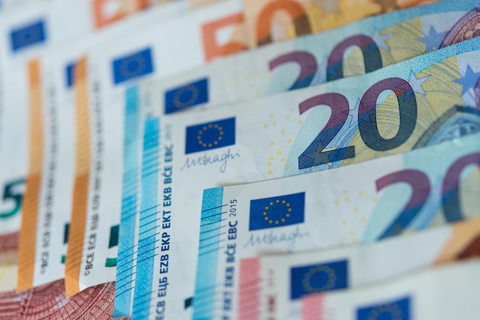 Zahlreiche Banknoten von 10, 20 und 50 Euro liegen sortiert auf einem Tisch.