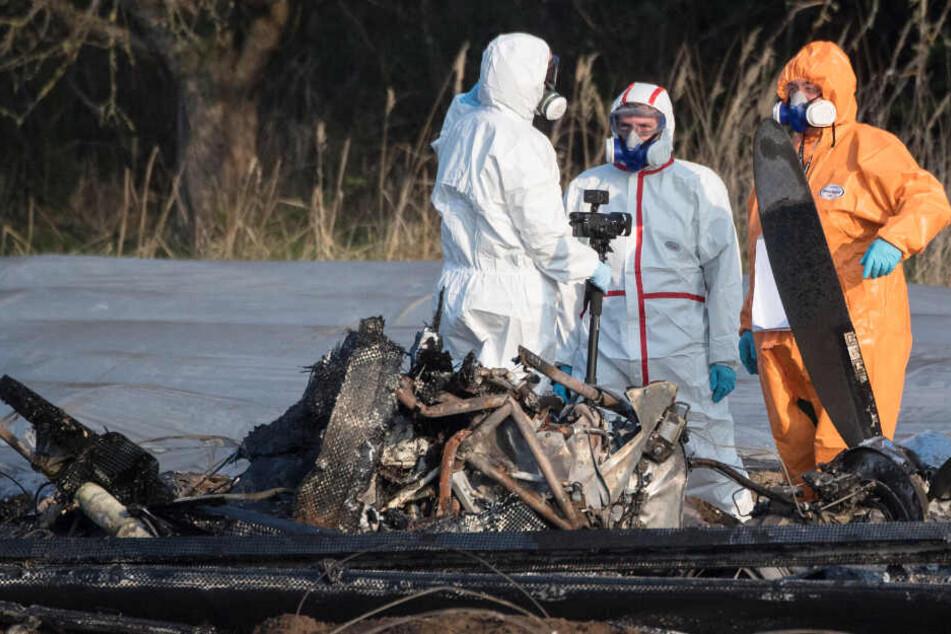 Beamte der Kriminalpolizei und Luftfahrtexperten der Bundesstelle für Flugunfalluntersuchung (BfU) untersuchen das Flugzeugwrack.