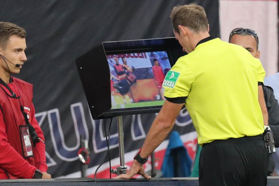 4. Spieltag: Schiedsrichter Sascha Stegemann (r) schaut sich eine Spielszene zwischen RB Lepzig und dem FC Bayern München mit Videobeweis auf einem Monitor an.