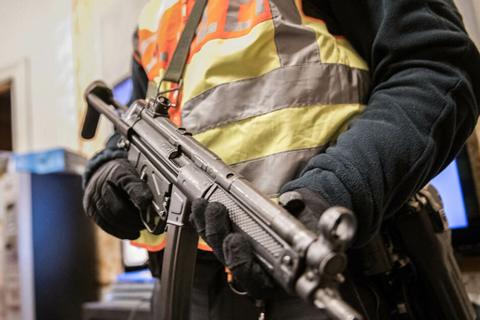 Ein Berliner Polizei mit seiner Dienstwaffe im Anschlag. (Symbolbild)