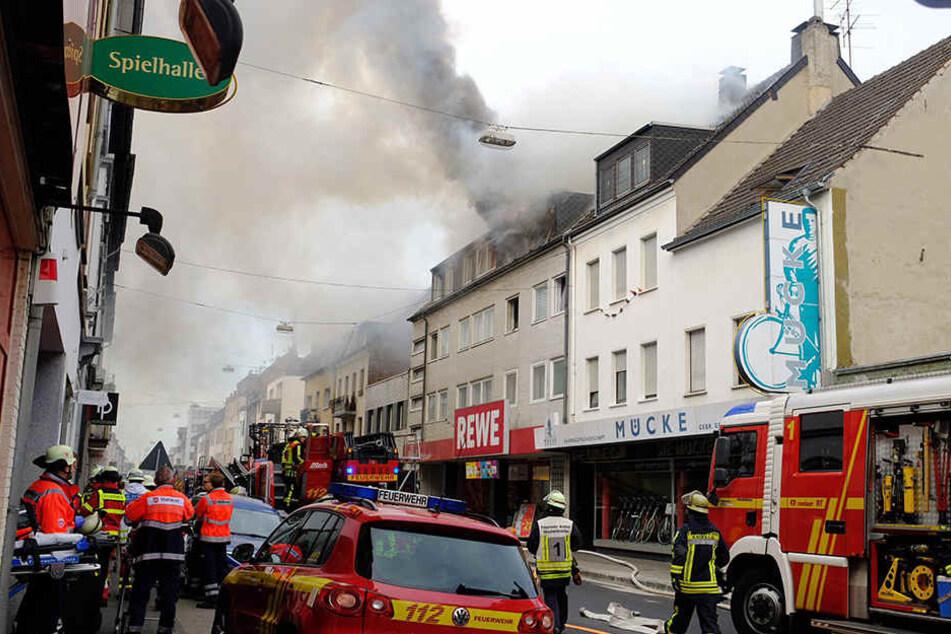 Feuerwehrleute löschen das Feuer in dem Wohnhaus in der Innenstadt von Krefeld.