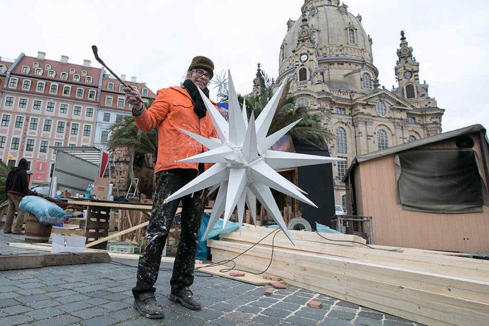 """Maler Charles Wiegmann (64) bringt am Neumarkt einen Weihnachtsstern an. Der """"Advent auf dem Neumarkt"""" öffnet am Donnerstag."""