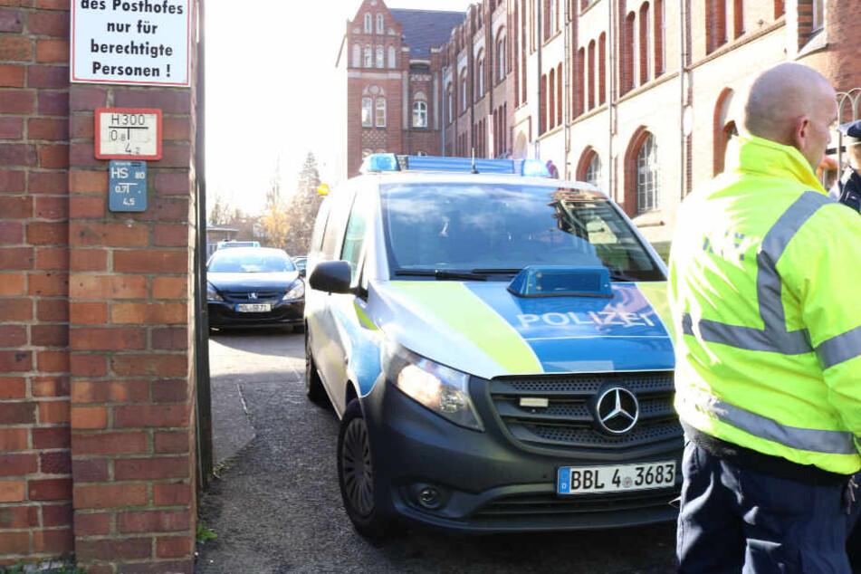 Polizisten sperren die Zufahrt zu dem Postgebäude in der Innenstadt ab.