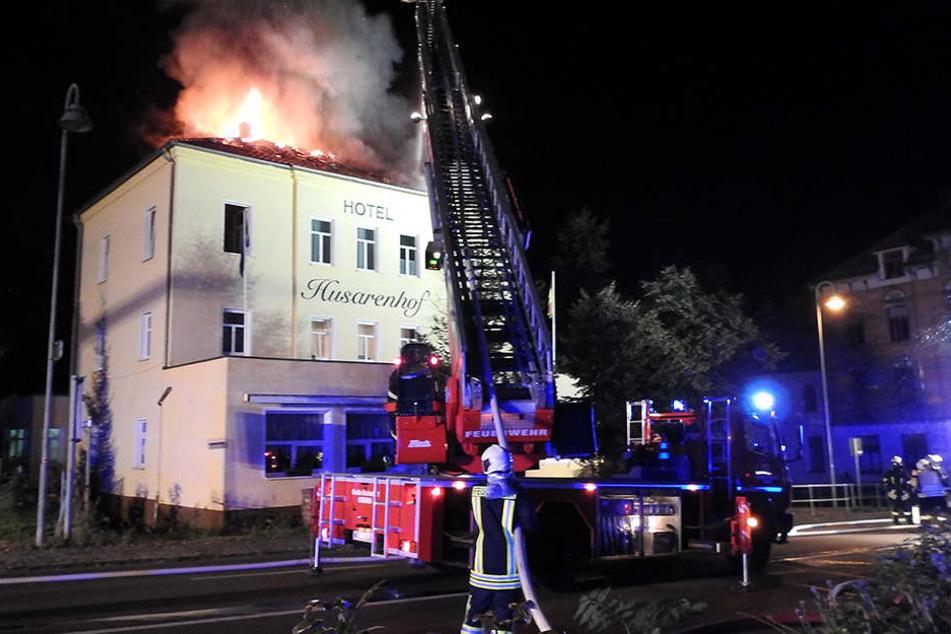 """Flammen schießen aus dem Dach des Hotels """"Husarenhof"""", Feuerwehrleute löschen  von der Drehleiter aus."""