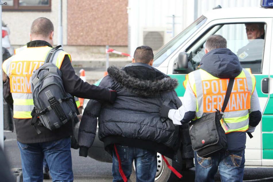 Polizisten begleiten einen straffällig gewordenen Asylbewerber zum Flughafen.