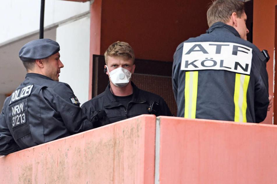 Polizisten und ein Feuerwehrmann der Analytischen Taskforce bei der Wohnungs-Durchsuchung in Köln-Chroweiler Mitte Juni.