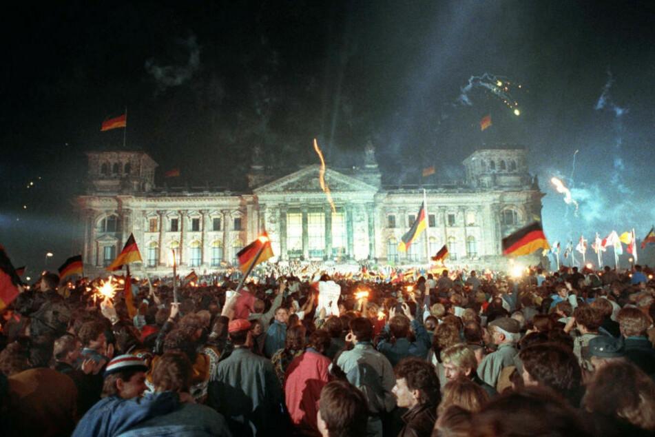 Jubelnde Menschenmassen vor dem Berliner Reichstag, die mit Feuerwerk, Deutschlandfahnen und Volksfesttrubel die wiedergewonnene Einheit Deutschlands am 3. Oktober 1990 feiern. 30 Jahre später beginnt am Samstag in Potsdam die große Einheits-Feier. (Archivfoto)