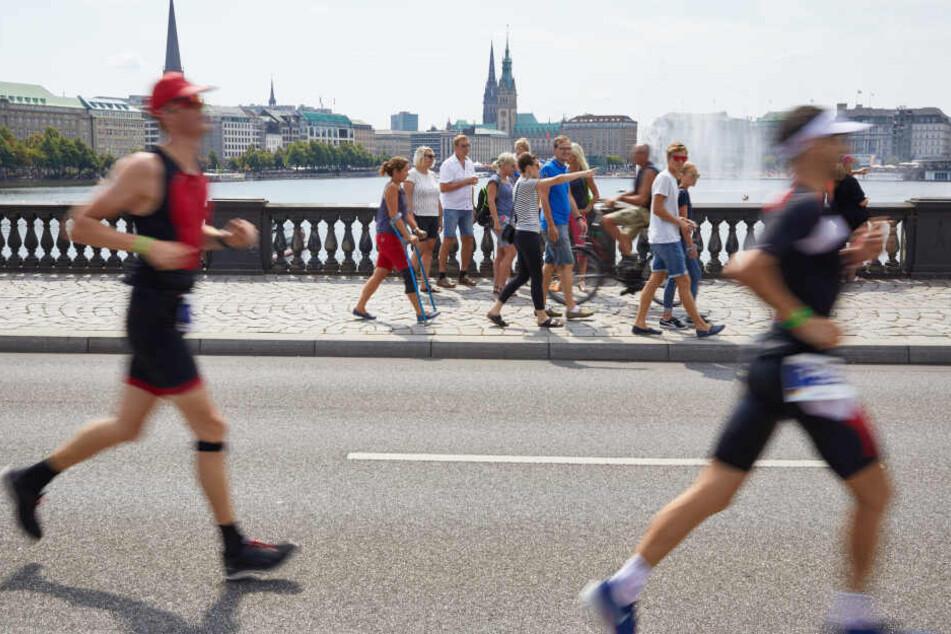 Triathleten laufen über die Lombardsbrücke. Im Hintergrund sind die Binnenalster und das Rathaus zu sehen.