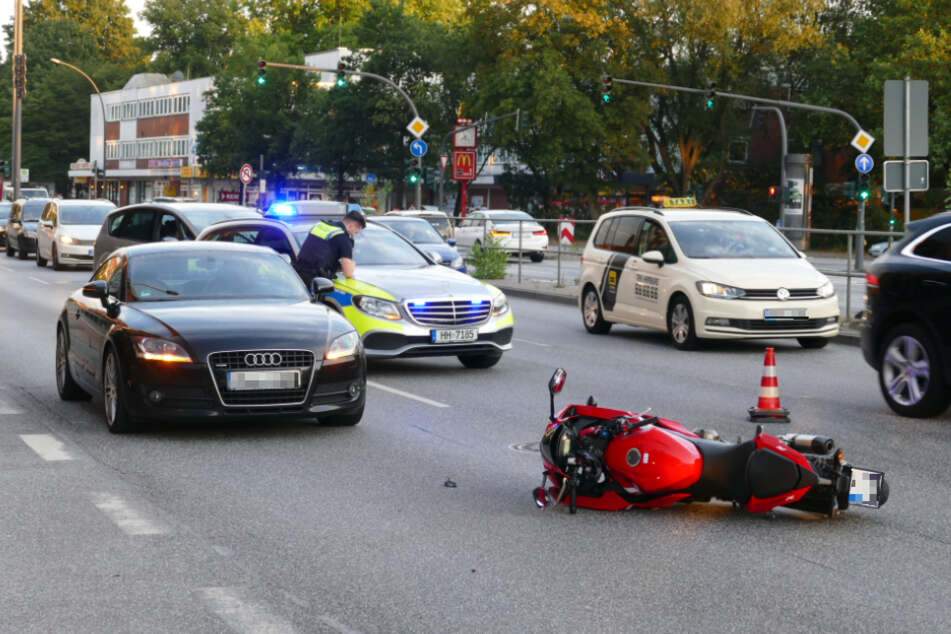 Nach dem Unfall liegt das beschädigte Motorrad auf der Straße, ein Polizist sichert den Unfallort.