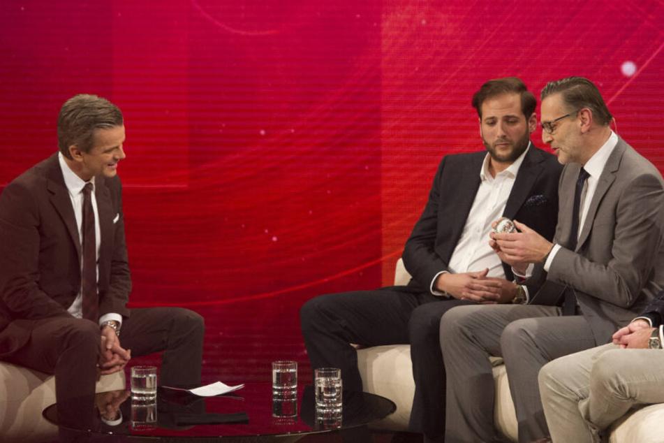 Markus Lanz (links) sitzt mit den Trödlern Detlev Kümmel (rechts) und Julian Schmitz-Avila an einem Tisch. (Archivbild)