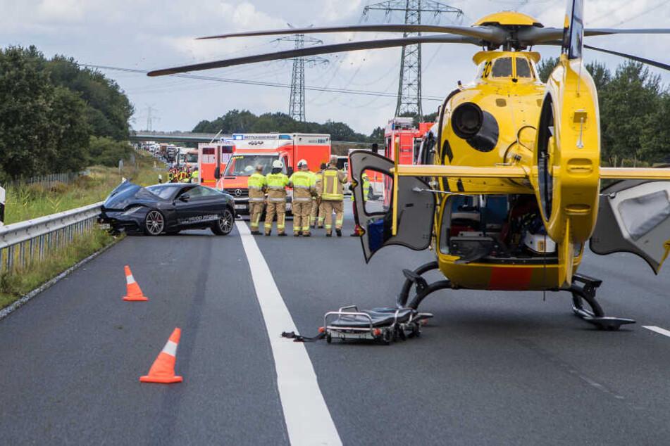 Ein Rettungshubschrauber steht auf der Autobahn. Ein Jaguar steht an der Leitplanke.