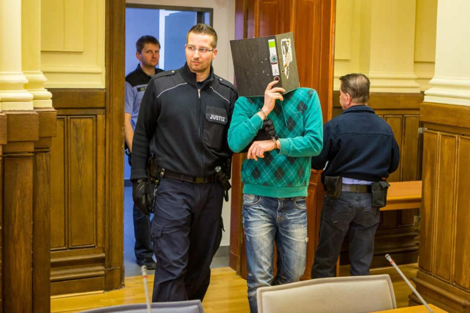Ein Wachtmeister führt den hinter einem Aktenordner versteckten Dirk K. in den Gerichtssaal.