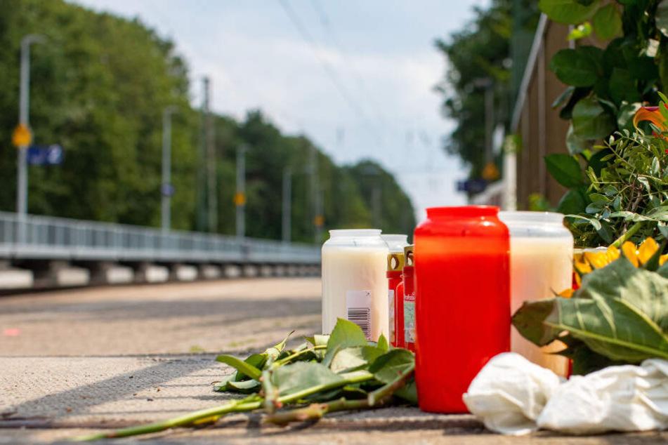 Blumen und Kerzen stehen an den Gleisen am Bahnhof.