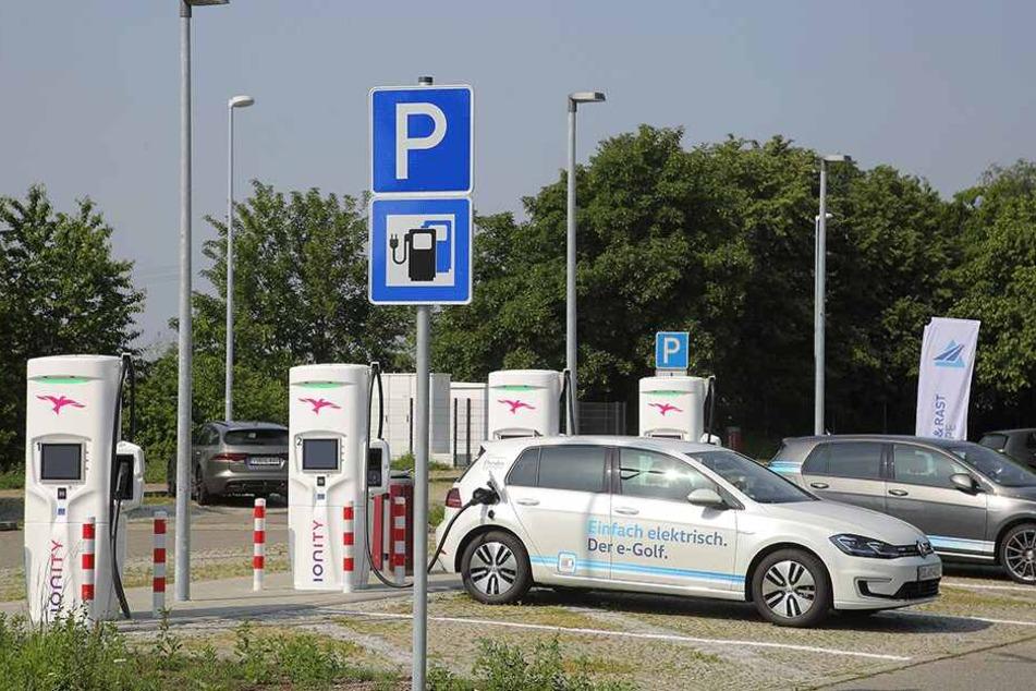 Schilder verweisen am Parkplatz hinter der Tankstelle auf die vier Superladesäulen.