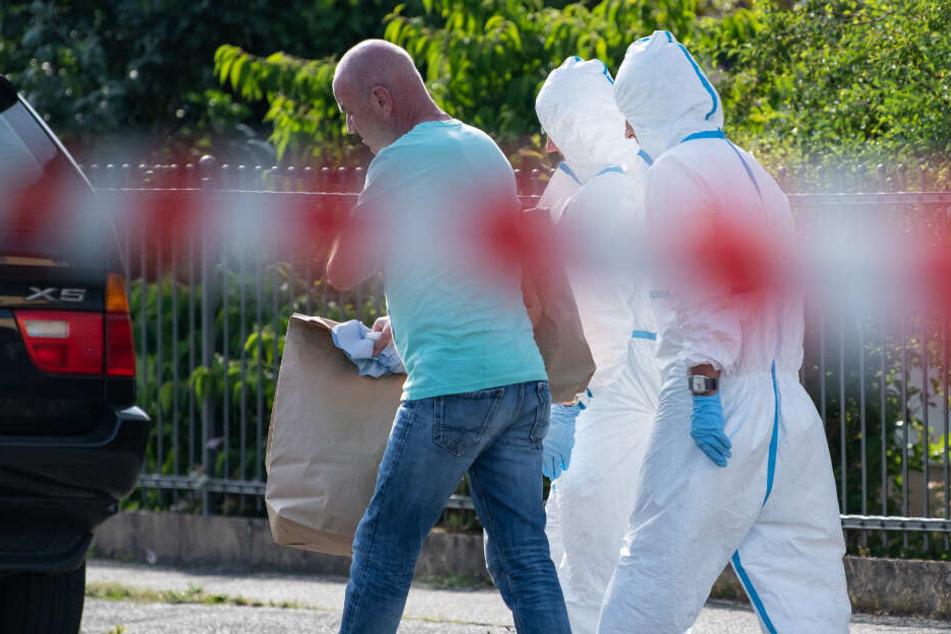 Mitarbeiter der Spurensicherung tragen Beweismaterial aus dem Einfamilienhaus.