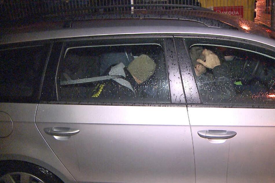 Der Tatverdächtige wird von Polizisten in einem Zivilfahrzeug mitgenommen.