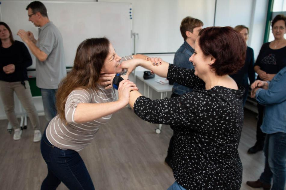 Die medizinische Fachangestellten Katja (links) und Iris üben bei einem Training, wie man sich aus einem Würgegriff befreien kann.