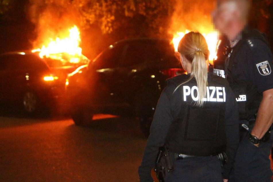 Polizisten stehen vor den brennenden Autos.