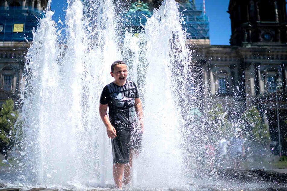 Abkühlung tut gut. Ein kleiner Junge genießt das kühle Nass in einem Springbrunnen.